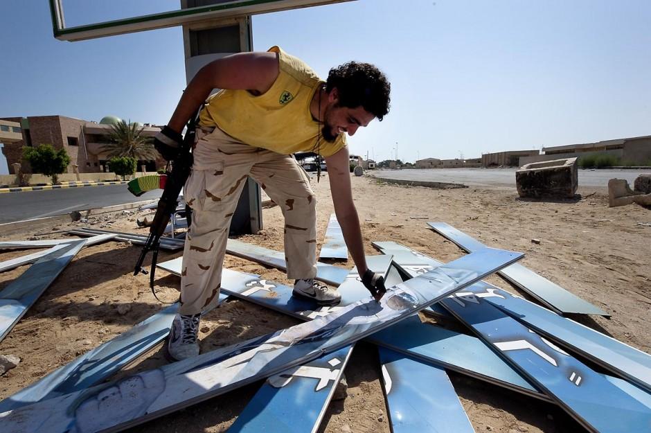 """27 août 2011 : Au poste frontière de Ras Jedir, les combattants berbères détruisent la dernière affiche de Kadhafi le jour leur victoire. le poste frontalier de Ras Jedir était jusq"""""""