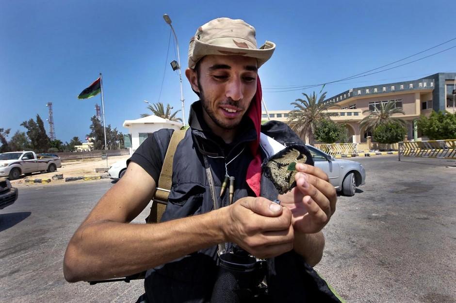 """27 août 2011 : Jallal, combattant rebelle berbère brule un insigne de la Libye de Kadhafi au poste frontalier de Ras Jedir le jour leur victoire. le poste frontalier de Ras Jedir était jusq"""""""